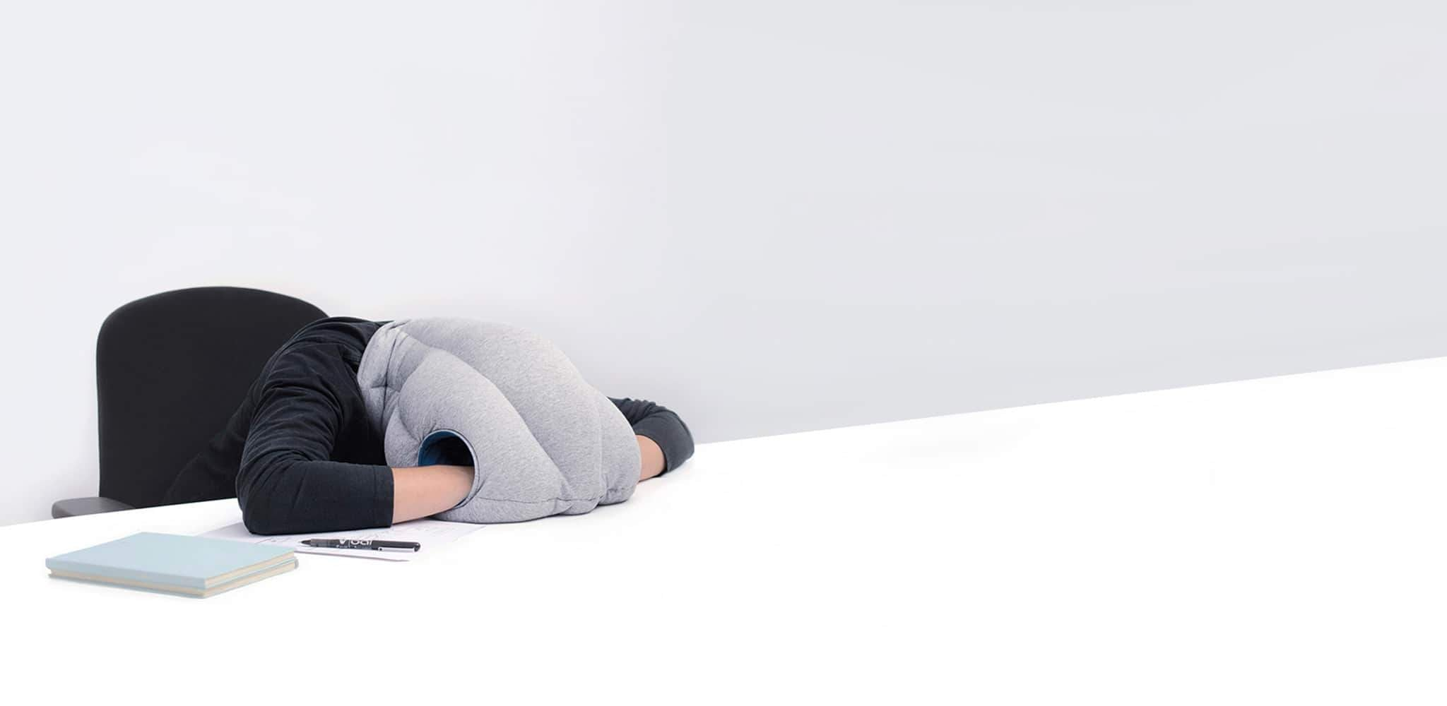 Person sleeping with their head laid forward on their desk while wearing the OstrichPillow Original.