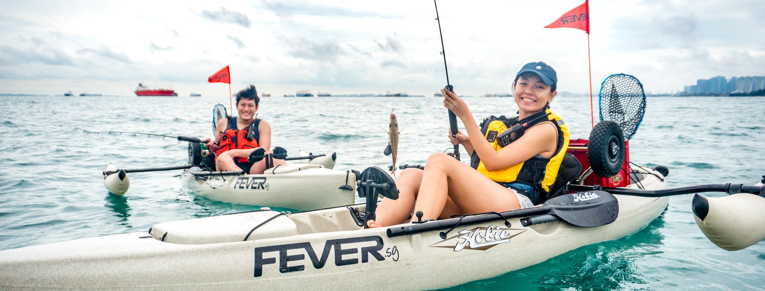 Man and woman in kayaks with woman holding up fish on a fishing rod