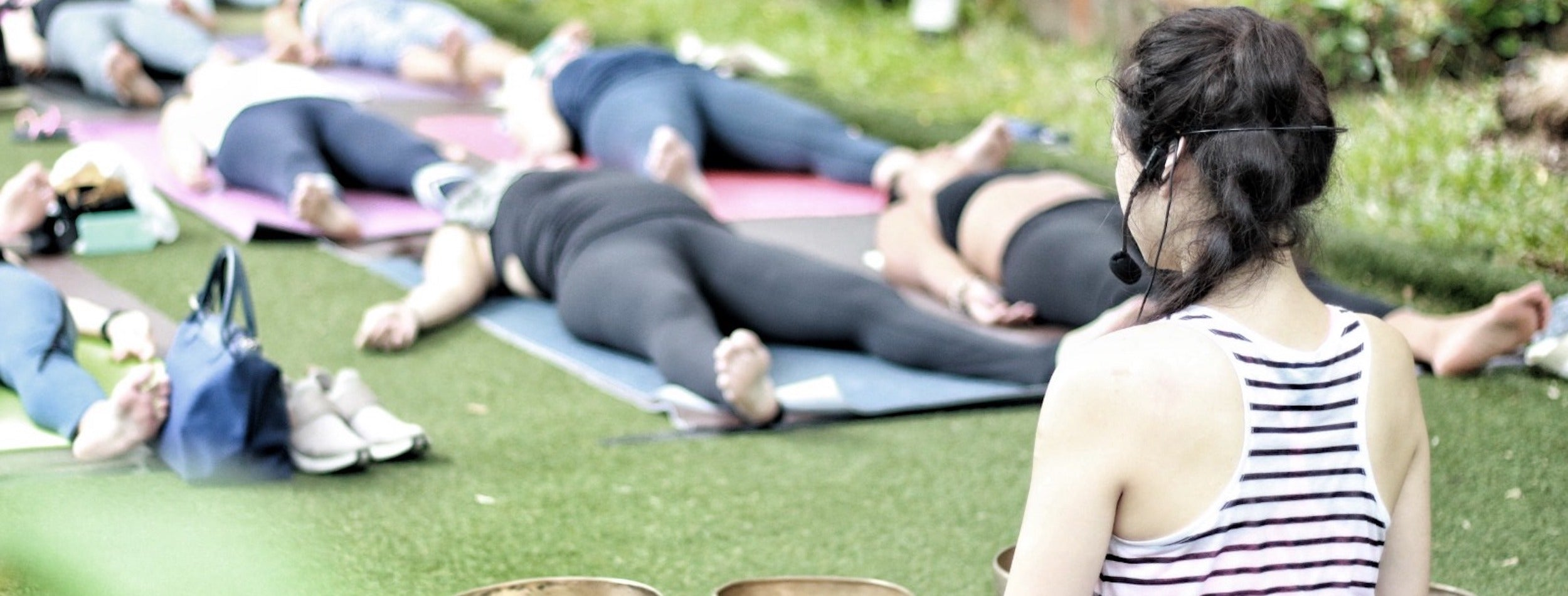 Woman with microphone playing music to a crowd of people laying down on yoga mats