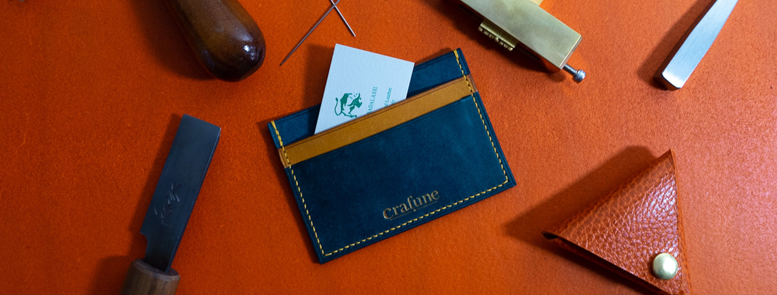 Blue leather cardholder on orange table surrounded by tools