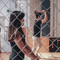 Two people throwing axes in an axe throwing venue