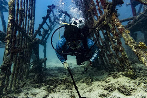 A scuba diver filming himself swimming through a cage underwater