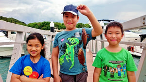 Three children, one of the holding up two fish