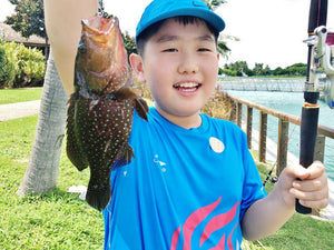 Young boy holding up a fish