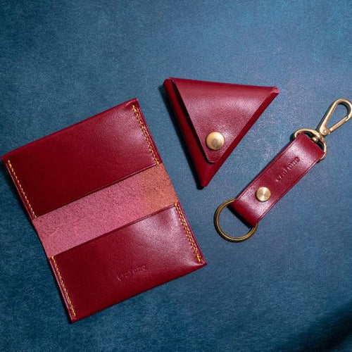 Red leather card sleeve, coin pouch, and key holder on a blue table