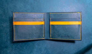 Open blue and yellow leather wallet on blue table