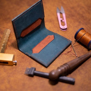 Blue leather wallet on table with other leather crafting tools