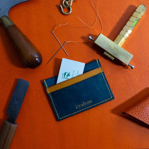 Blue and yellow leather cardholder on orange table surrounded by leather crafting tools