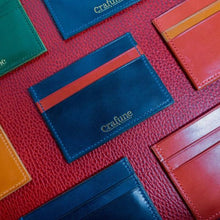 7 leather card holders of different colours on a red table