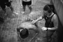 Woman helping man with breathing exercise in swimming pool