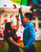 Man and woman holding an umbrella as red leaves fall down on them