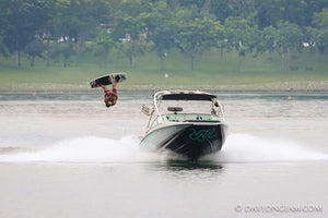 A man backflipping on a wakeboard with a boat