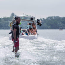A man wakeboarding with a boat in the background