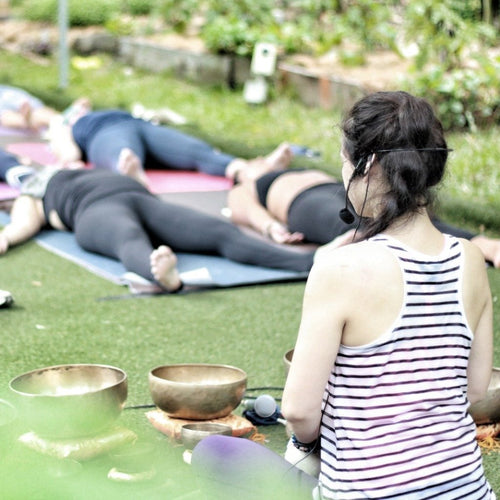 Woman playing singing bowls as people lay on the ground