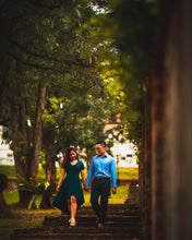 Man and woman holding hands walking through a park