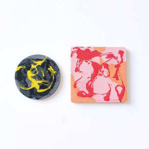 Two marble coasters flat on a table: A pink square and a grey / gold circle