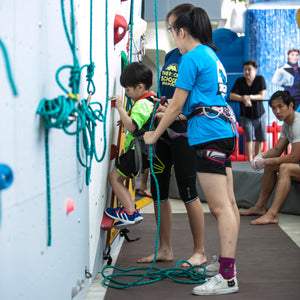 Woman and man helping young boy on rock climbing wall