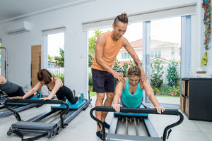 Man helping woman on pilates machine