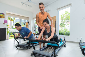 Man helping man and woman on pilates machines