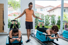 Man helping two women on pilates machines