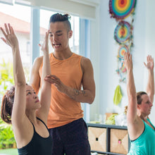 Man helping two woman with yoga poses