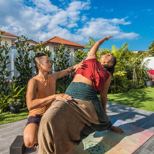 Man helping woman with yoga pose
