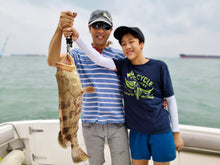 Man and boy holding up a fish