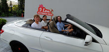 Three people in white convertible