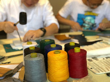 Many coloured reels of string as people work on leather in the background
