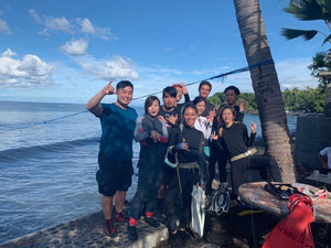A group of people at the ocean with scuba diving gear
