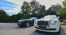Two Rolls Royce cars: One black and one white