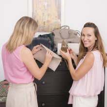 Two women looking at handbags
