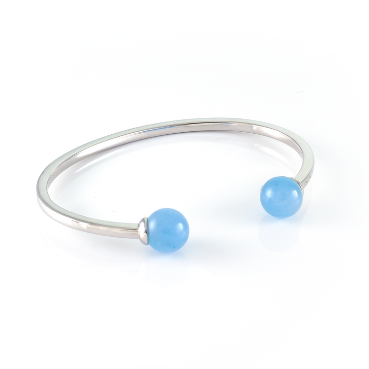 Xtinctio - Bangle Sterling Silver dipped Platinum  and Blue Chalcedony stone.  Imbued with the spirit of the Ocean and serving as a constant reminder that in this age of extinction, we are all connected to every living thing.  Our partner in Ocean Conservation is The Coral Reef Restoration.