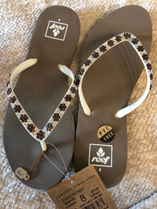 tan/white reef flip flop with flower pattern