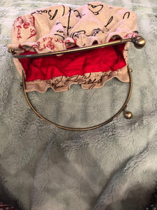 vintage purse with red lining and cross charm