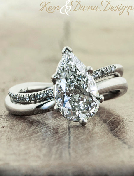 modern pear shaped diamond ring with band;caption:2.09ct. Pear Diamond Platinum paired with Bella wedding band