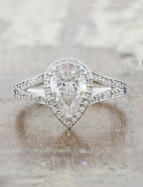 Halo engagement ring with pear shaped diamond and a split band caption: 1.56ct. Pear Diamond Platinum