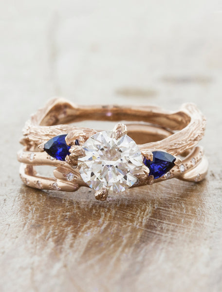 Nature inspired three stone setting. caption:1.00ct. Round Diamond and Sapphire 14k Rose Gold, customized with bark texture. Shown with Selene wedding band