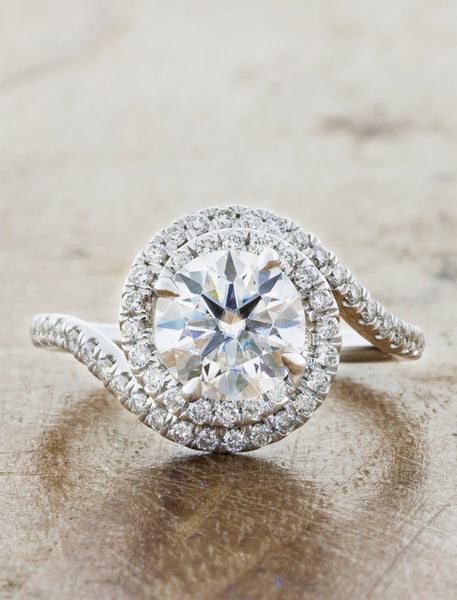 assymetrical swirling halo engagement ring. caption:Shown with 1.25ct diamond option