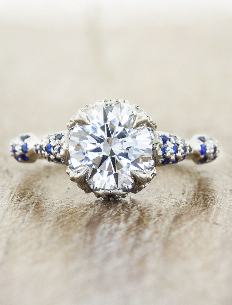 intricate round diamond engagement ring, platinum band with sapphire accents