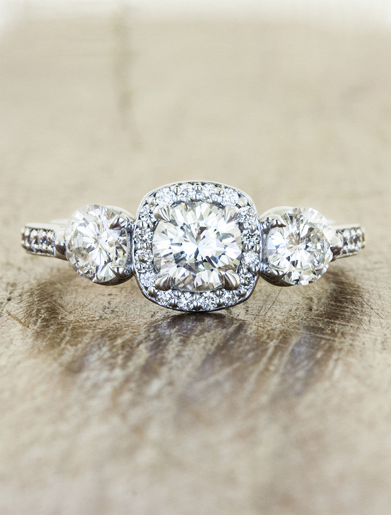 vintage-inspired three stone diamond ring, halo. caption:Shown with 0.45ct center diamond