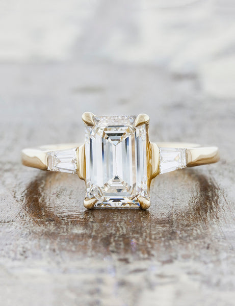 Three stone tapered baguettes;caption:Customized with an 1.70ct. Emerald Cut Diamond 14k Yellow Gold