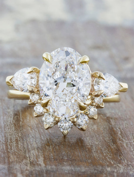 Oval diamond three stone engagement ring, pear side diamonds. caption:3.00ct. Oval Diamond 14k Yellow Gold paired with a custom Antoinette wedding band