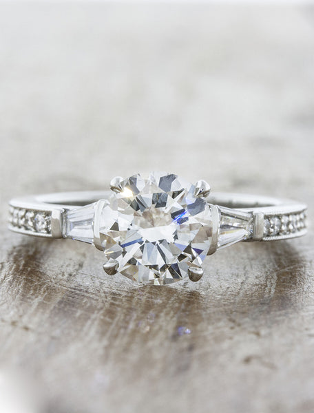 Three stone tapered baguettes;caption:1.50ct. Round Diamond Platinum. Customized with diamond pavé band.