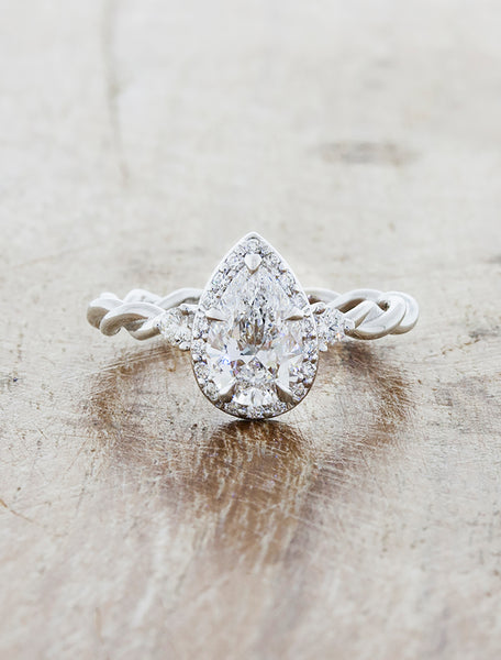 caption:Custom Nolah, no diamonds on band, set with 0.83ct pear shape diamond