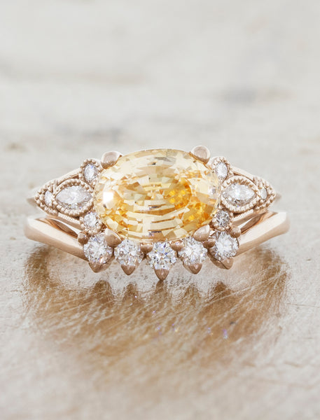 caption:Set with peach color sapphire and paired with Antoinette wedding band