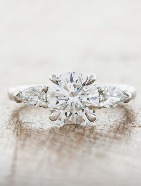 Oval diamond three stone engagement ring, pear side diamonds;caption:1.15ct. Round Diamond Platinum