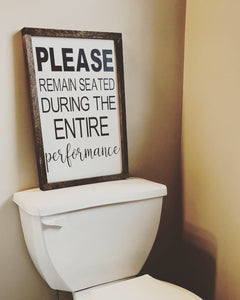 Please remain seated bathroom sign
