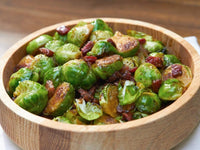 Brussels sprouts with lardons in a wooden bowl.