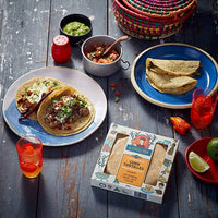 A spread of tacos with a pack of La Tortilleria Corn Tortillas on a rustic wooden table.